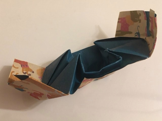 """Chinese Junk (Gondola):  Turquoise and patterned 6 inch kami square. Folder: British man Folded likely June 2019.  Source article: Frog Base, History of Paperfolding-German, Is the Junk Chinese? A talk by Kunihiko Kasahara. Likely Asian. An odd folded model in the shape of a ship with two flat ends, made by a """"Pull-out"""" technique where pulling out a flat piece of paper in the final step leads to a three-dimensional final model. There are some variations to it, including """"The Ship of the King and Queen"""" from Spain in a barge shape, and the """"Treasure Ship"""" from Japan with a pointed bow. An intermediate fold in the process is a box-live (?) shape called """"The Buckle"""" or """"The Bar and Bolt."""""""