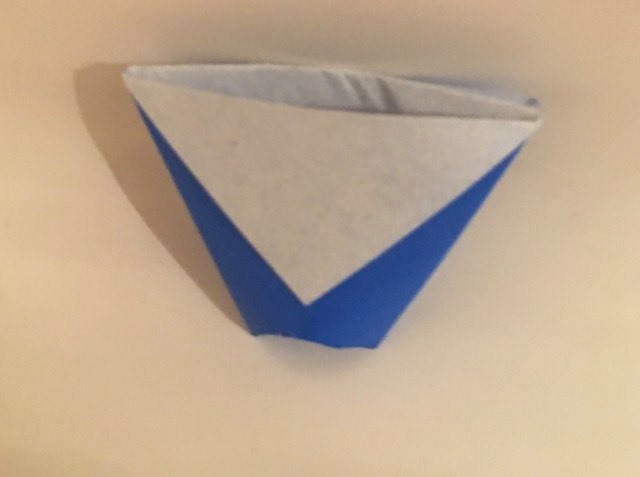 Cup: Blue 2 inch square kami. Folder: Lisa B. Corfman. Folded: August 9, 2020. Source article: A Talk by Kunihiko Kasahara.  A simple model, which Lillian Oppenhiemer's grandson Tom folded for a school project. He folded 50 cups to share with all his friends which inspired Lillian to focus on sharing Origami in the future work of the Origami Center.
