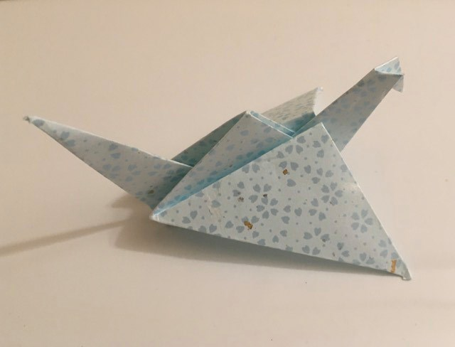 """Flapping Bird:  Light blue 6 inch square, Hana Fubuki washi. Folder: Lisa B. Corfman. Folded August 9, 2020. Likely between 1860's-1870's. Likely western origin. Source article: Origins of the Flapping Bird, The Mobil Pegasus  Similar design to a Crane, but the wings are folded at an angle instead of straight down.  Pulling the tail down causes the wings to flap, magicians would use the bird in tricks, by bringing a seemingly ordinary piece of paper on stage, making a few folds, then having it flap to the delight of the audience. It was introduced in the West around the same time as the Jumping Frog, another action model. A version of this model was used as a promotional item by Mobil Oil Company, as a red sheet with instructions that kids could fold up into the """"Mobil Pegasus."""""""