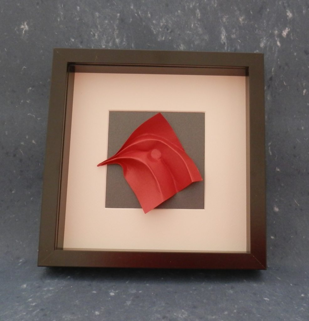 CHICK HEAD Wet folded red Stardream paper. Donated to Mujeres de Papel exhibition in EMOZ, Zaragoza, Spain 2016.  I explore ideas in the process of folding paper. Movements in folds are my meditation. Color of paper often defines the mood of my conversation with paper. What you see is the result of it.